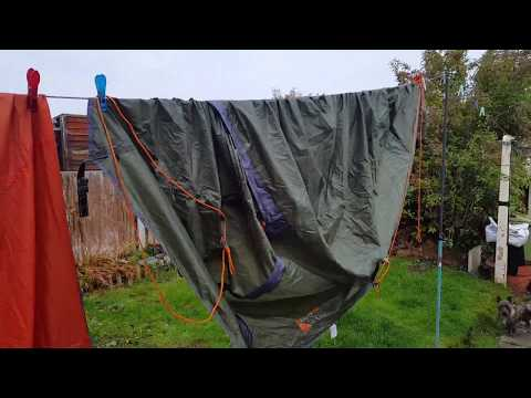 Cleaning a tent after a muddy wild camp.