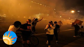 Protesters vandalize downtown building as Police fire smoke bombs.