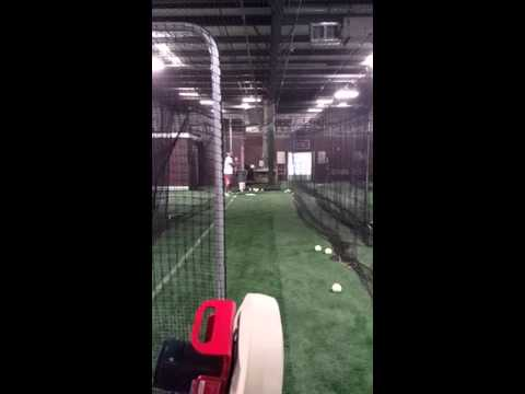 Softball Machine pitching a curveball to Juan