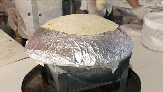 A uniformed man cooking rumali roti in his kitchen stove over a foil sheet