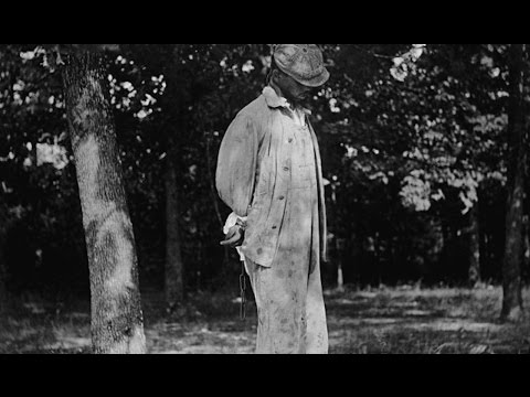 This is a Black man being hung from a tree with his tied behind his back during the 20th century and is used to demonstrate racial terror.