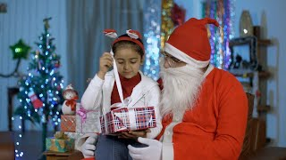 Adorable Indian girl opening her Christmas gift while sitting with happy Santa in India