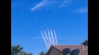 F-16 jets fly in formation over a residential neighborhood for an air show.