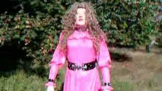 TV ouside in pink PVC dress and female mask