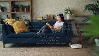 Robotic vacuum cleaner is hoovering wooden floor of modern loft style aparment moving around carpet