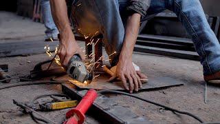 An Indian labor cutting off an iron sheet using a iron cutter machine