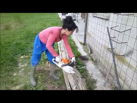 Woman with Chainsaw Stihl MS241C Cutting An Ancient Cedar Beam