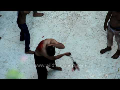 Shia Muslims flagellate themselves with chained knife
