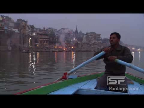 Medium tight shot of man rowing a boat on the foggy Ganges river in India