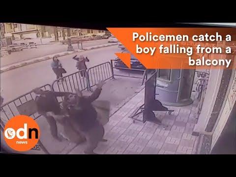 Three policemen catch a boy falling from a balcony