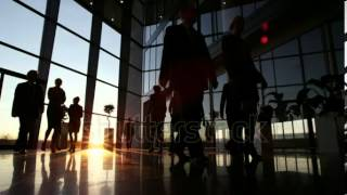 stock footage silhouettes of a diverse group of business people walking through a modern glass front