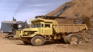 Tractor crane dumps rock into large dump truck for transferring rock to rock crus...HD Stock Footage
