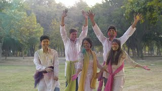 Group of young cheerful friends celebrating Holi festival together in a park - festive scene
