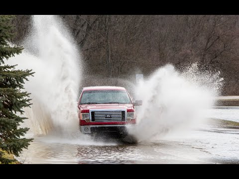 Motorists drive through flood water in Lowell