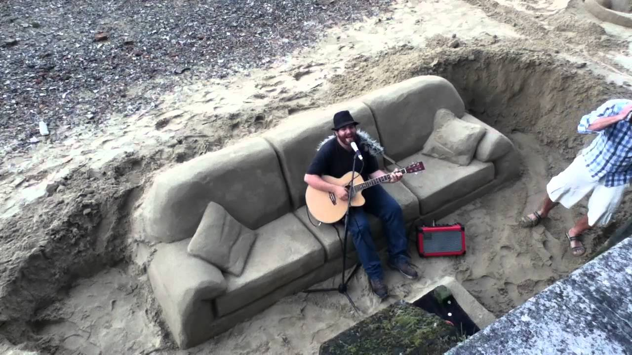 A Guy Singing A Song On A Sand Sofa