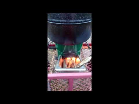 StoveTec rocket stove with custom feed to limit sparks/embers falling out of stove. Steaming squash
