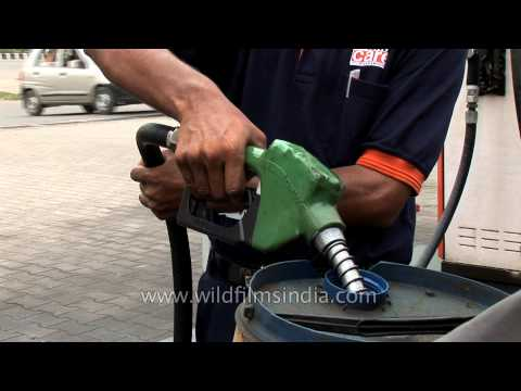 Man fills diesel in a drum at a IBP petrol pump, India