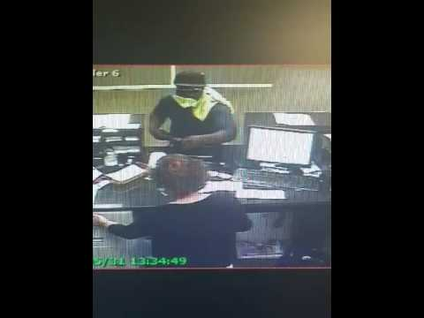 Video show robber pulling out a plastic bag and taking a handful of cash from the teller.