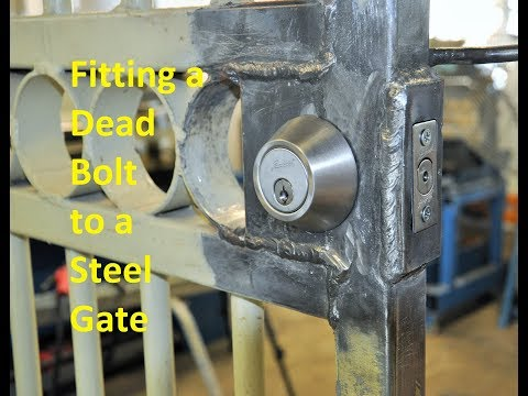 Fitting a dead bolt to a steel gate.
