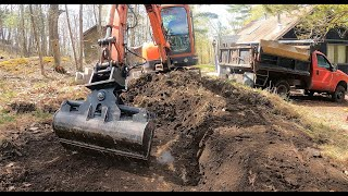 Hammering a drainage trench behind a house