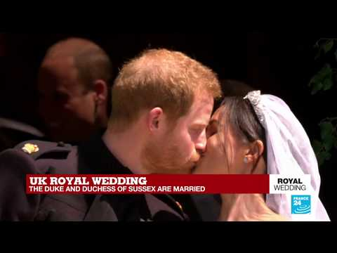 The Duke and Duchess of Sussex kiss in front of St George's Chapel as they exit