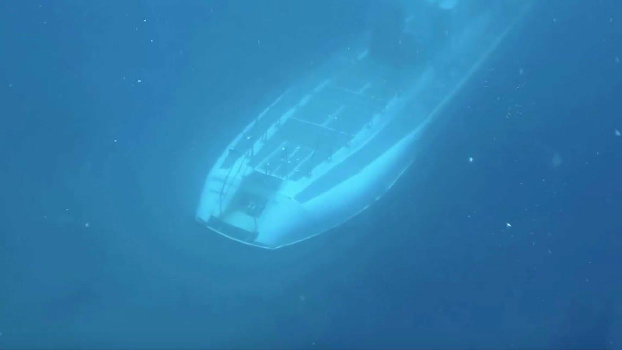 Spooky moment: Submarine passes beneath scuba divers