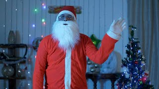 Indian Santa looks at the camera and waves his hand - greeting gesture on Christmas