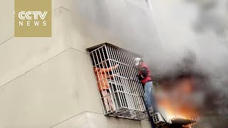 Man climbs three stories to rescue woman trapped by fire