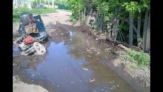 Трактор вытаскивает мотоблок с грязи.