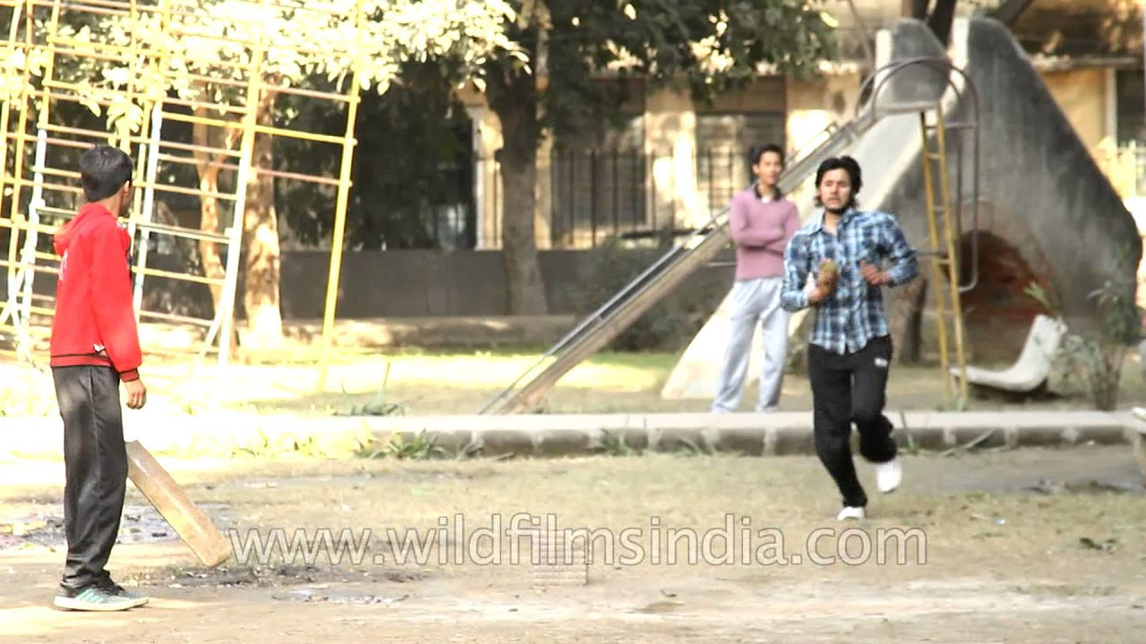 Children playing cricket at a park in India