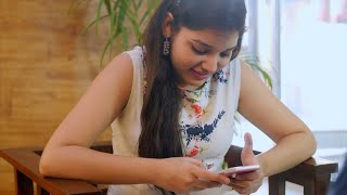 Beautiful Indian girl scrolls her mobile phone while sitting in a restaurant