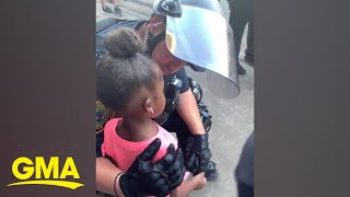 Police officer comforts little girl after she asks: 'Are you going to shoot us?' l GMA Digital