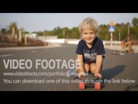 Smiling little boy rides sitting on skateboard in slowmotion. Video stock footage