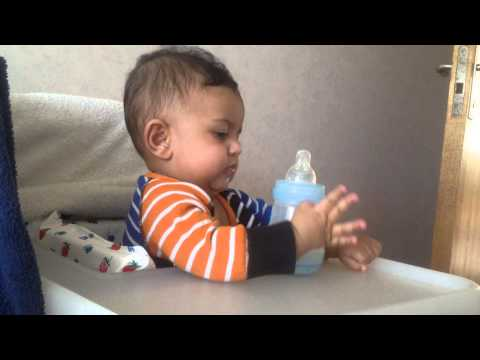 4 month old trying to hold his bottle . amazing baby