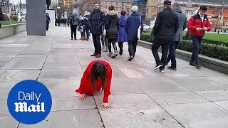 Mystery lady in red spotted crawling outside parliament