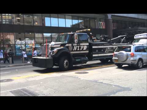 GIANT NYPD TRAFFIC ENFORCEMENT HEAVY WRECKER TOWING BROKEN DOWN COMMUTER BUS ON W. 42ND ST. IN NYC.