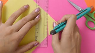 Overhead shot of a girl cutting a yellow chart paper with a cutter
