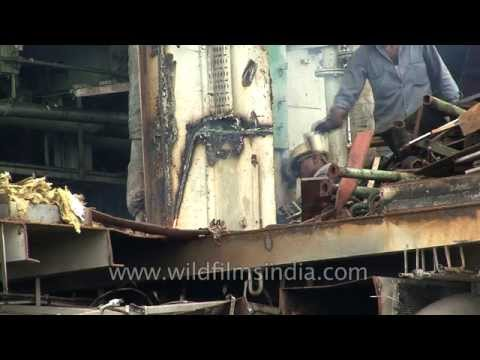 Indian workers dismantle ship at Alang ship breaking yard - India