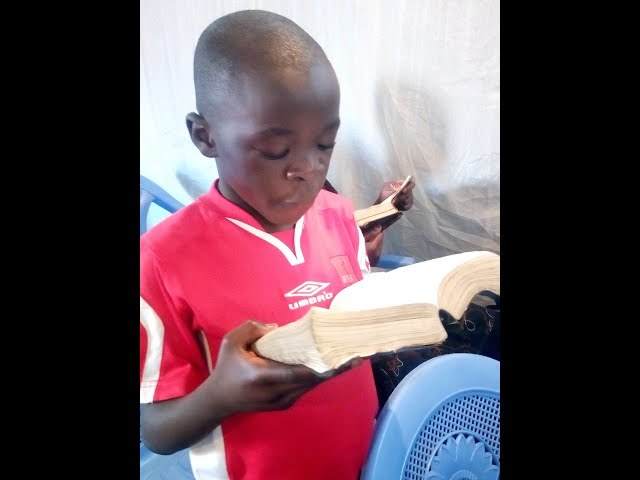 Child Reading the Bible @ GMFC / WFF Kibera Slum