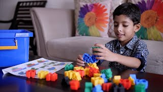 Cute little Indian boy/kid playing alone with colorful plastic building blocks at home