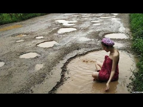 Thai women take dip in the road in pothole protest