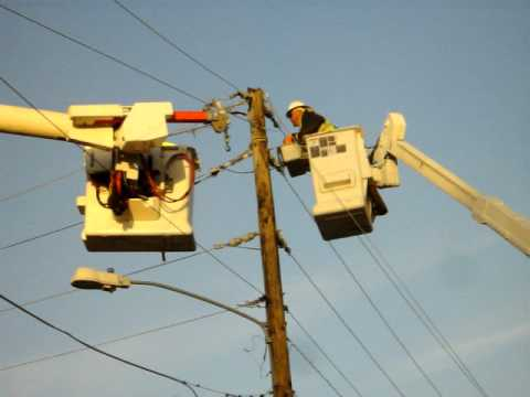 Power crews work to repair a power pole