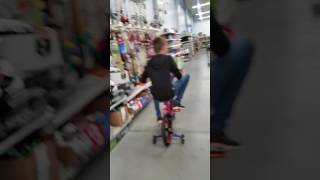 Savage kid rides bike in Walmart in front of workers