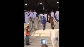 فيديو.. رجل أمن یحمل مُسناً لمساعدته على صعود الدرج بالمسجد الحرام