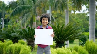 Cute Indian kid happily smiling while holding a blank placard in a public park