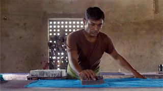 Slow-motion shot of a man block printing on a blue cloth