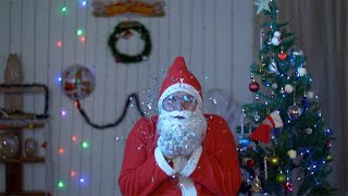 Happy Santa Claus celebrating Christmas while blowing up confetti near a Christmas tree