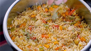 Closeup shot of an Indian female sprinkling dried coriander leaves on vegetable rice