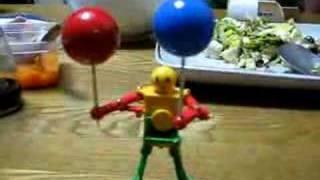 分子模型用の玉を両手に持ってパラパラを踊るロボット(315円)