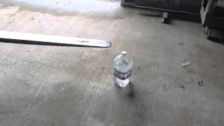 amazing forklift tricks picking up a coin with a forklift and placing it on top of a water bottle